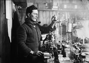 In the interior of the hut, Atkinson, smoking a pipe, stands at a bench holding up a test tube. On the bench are a microscope and numerous bottles, jars and test tubes.